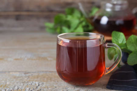 Cup with hot aromatic mint tea on wooden table. Space for text