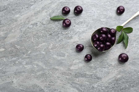 Fresh acai berries and spoon on light gray table, flat lay. Space for text