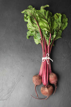 Raw ripe beets on black slate table, top view