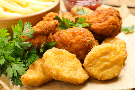 Tasty deep fried chicken pieces and nuggets on parchment, closeup Foto de archivo