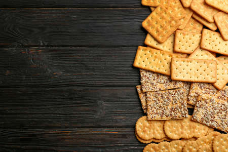 Many delicious crackers on wooden table, flat lay. Space for text