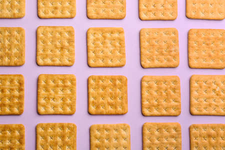 Delicious crackers on violet background, flat lay