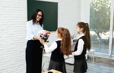 Schoolgirls congratulating their pedagogue with bouquet in classroom. Teacher's day Standard-Bild