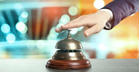 Man ringing hotel service bell on blurred background, closeup. Banner design