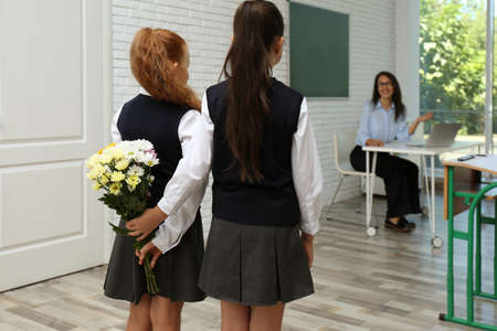 Schoolgirls with bouquet congratulating their pedagogue in classroom. Teacher's day