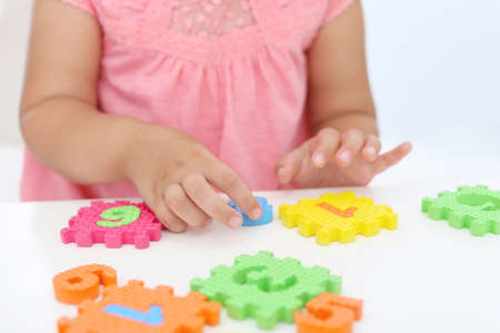 Little girl playing with colorful puzzles at white table, closeup. Educational toy Zdjęcie Seryjne