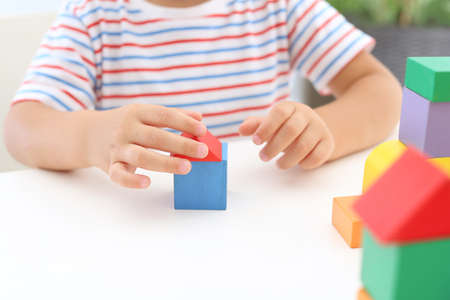 Little boy playing with colorful blocks at white table, closeup. Educational toy