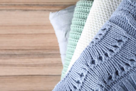 Stack of folded warm sweaters on wooden table, top view