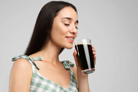 Beautiful woman with cold kvass on light gray background. Traditional Russian summer drink