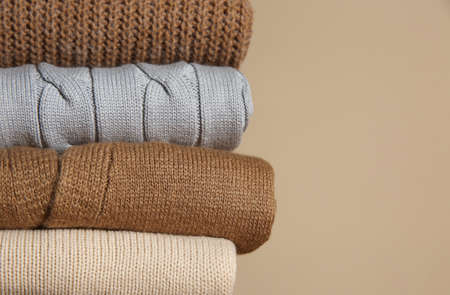 Stack of folded knitted sweaters on beige background, closeup. Space for text
