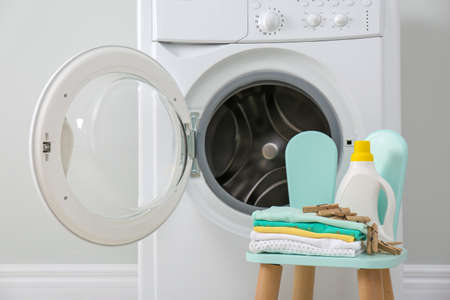 Bottle of detergent and children's clothes on chair near washing machine