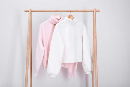 Stylish knitted sweaters hanging on clothing rack near light wall