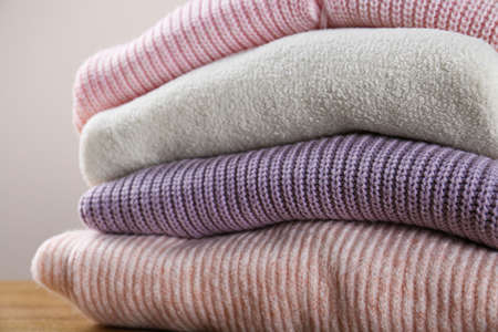 Stack of knitted sweaters on wooden table, closeup