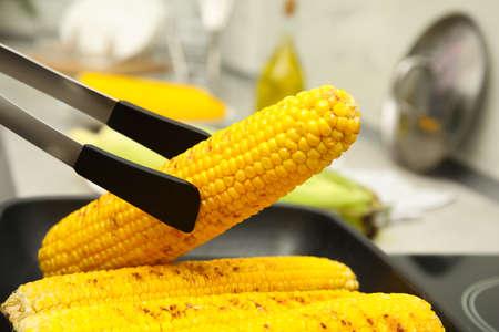 Cooking fresh corn cobs on grill pan closeup