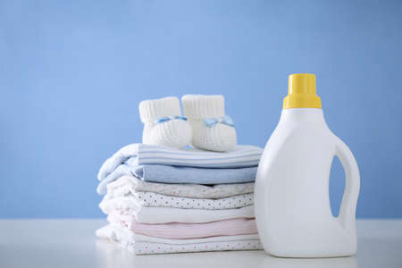 Detergent and children's clothes on white table near blue wall 版權商用圖片