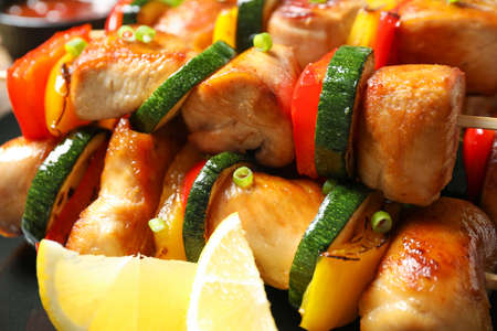 Delicious chicken shish kebabs with vegetables and lemon on plate, closeup