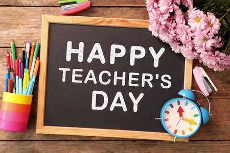 Small blackboard with text Happy Teacher's Day, stationery and flowers on wooden table, top view