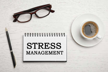Text Stress Management in notebook on table with eyeglasses, pen and cup of coffee on white wooden table, flat lay