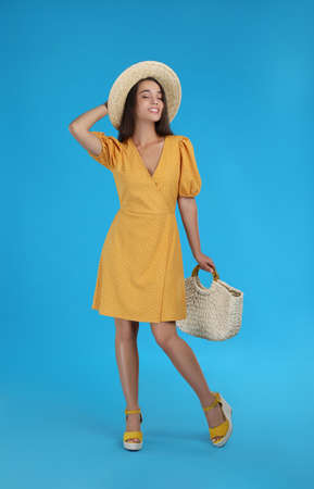 Young woman wearing dress with straw bag on light blue background