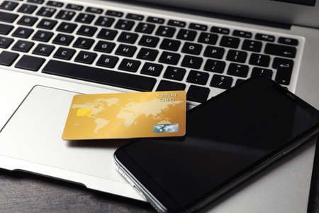Credit card, smartphone and laptop on table, closeup