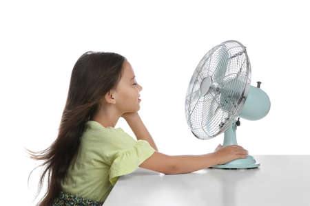 Little girl enjoying air flow from fan on white background. Summer heat