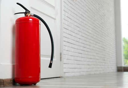 Fire extinguisher on floor near door indoors, space for text