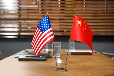 USA and China flags on wooden table in office. International relations Foto de archivo
