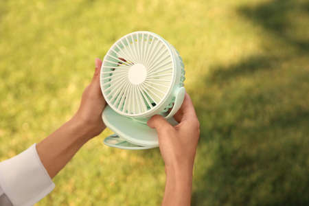 Woman holding portable fan outdoors on sunny summer day, closeup. Space for text