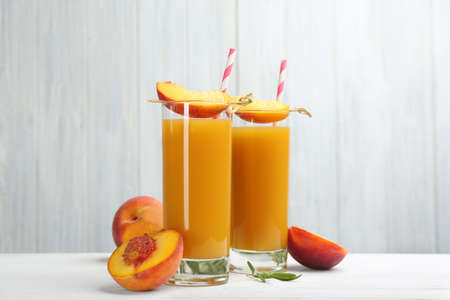 Natural peach juice and fresh fruits on white wooden table
