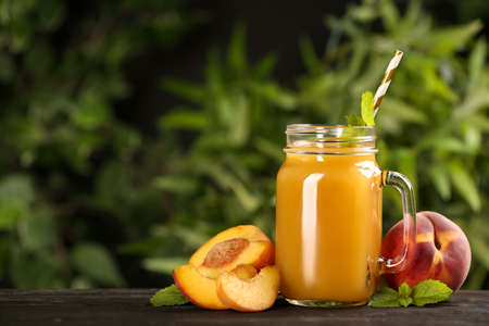 Natural peach juice and fresh fruits on wooden table. Space for text