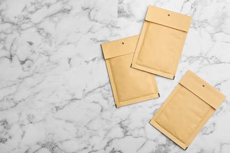 Kraft paper envelopes on white marble background, flat lay. Space for text