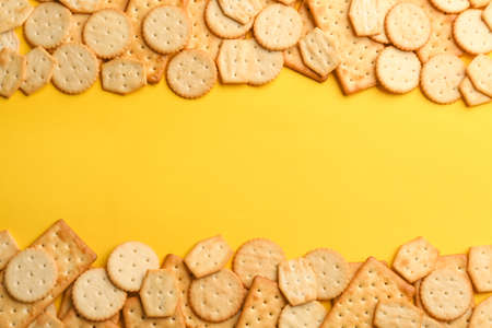 Delicious crackers on yellow background, flat lay. Space for text