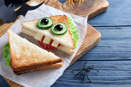 Cute monster sandwich served on blue wooden table, closeup. Halloween party food