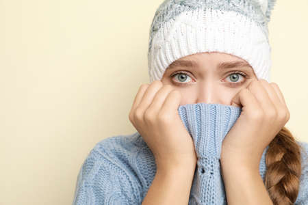Young woman wearing hat suffering from fever on light background, space for text. Cold symptoms