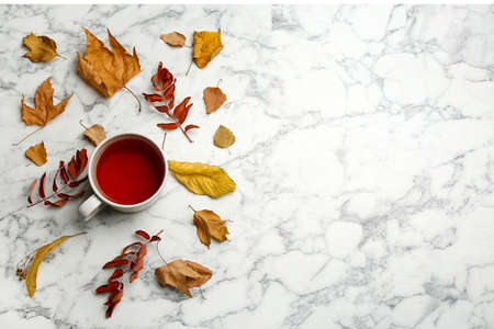 Flat lay composition with cup of hot drink and autumn leaves on white marble background, space for text. Cozy atmosphere