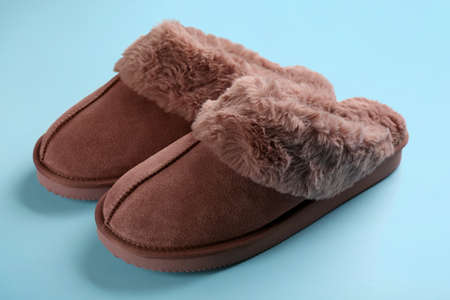 Pair of stylish soft slippers on light blue background