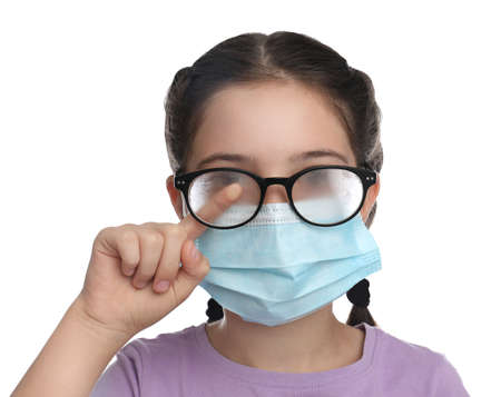 Little girl wiping foggy glasses caused by wearing medical face mask on white background. Protective measure during coronavirus pandemic Banque d'images
