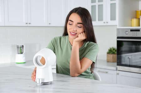 Woman enjoying air flow from portable fan in kitchen. Summer heat