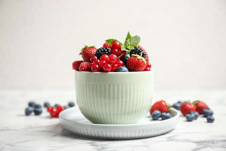 Mix of ripe berries on white marble table