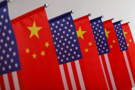 USA and China flags on light background, closeup. International relations Foto de archivo