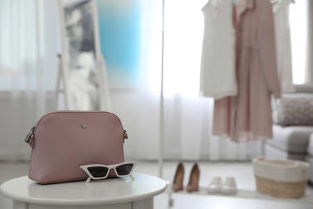 Stylish woman's bag and sunglasses on table in room. Space for text