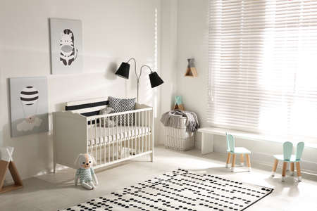 Cute baby room interior with crib and decor elements Standard-Bild