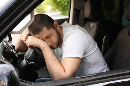 Tired man sleeping on steering wheel in his car Stock fotó