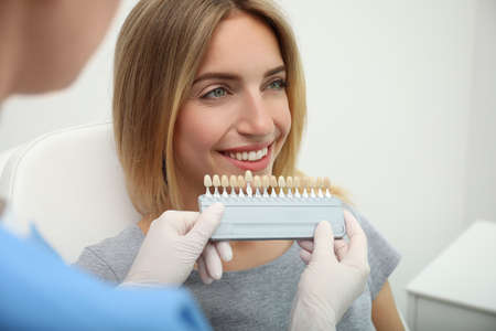 Doctor matching patient's teeth color with palette in clinic, closeup. Cosmetic dentistry