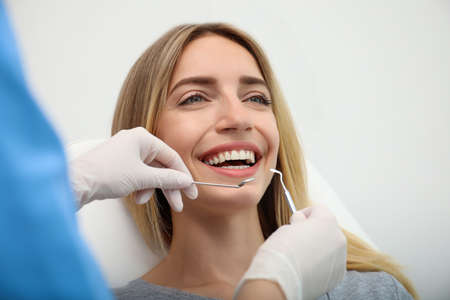Doctor examining patient's teeth on light background, closeup. Cosmetic dentistry Archivio Fotografico