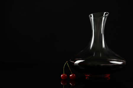 Delicious cherry wine and ripe juicy berries on black background. Space for text