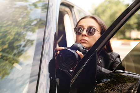 Private detective with camera spying near car outdoors Imagens