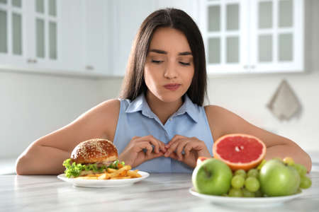 Woman choosing between fruits and burger with French fries in kitchen