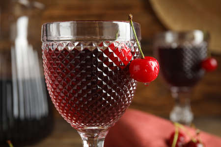 Delicious cherry wine with ripe juicy berries on blurred background, closeup