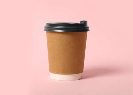 Takeaway paper coffee cup on pink background